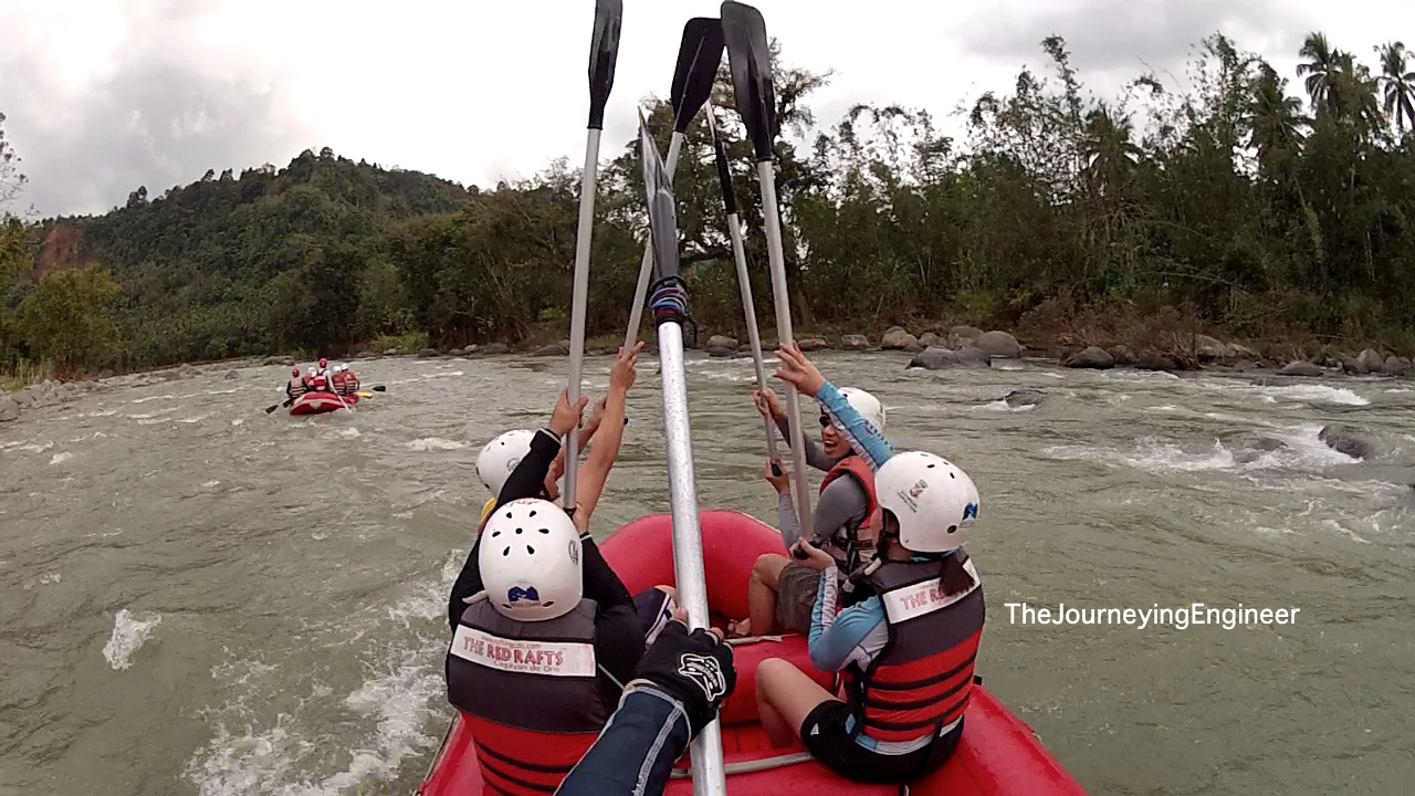 Group of tourists on raft paddle toasting Cagayan de Oro